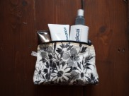 Lisa Stickley wash bag with Piz Buin suncream and Dermalogica skincare